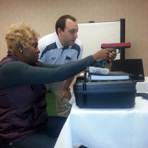 Student learning to aim a pistol with certified instructor.